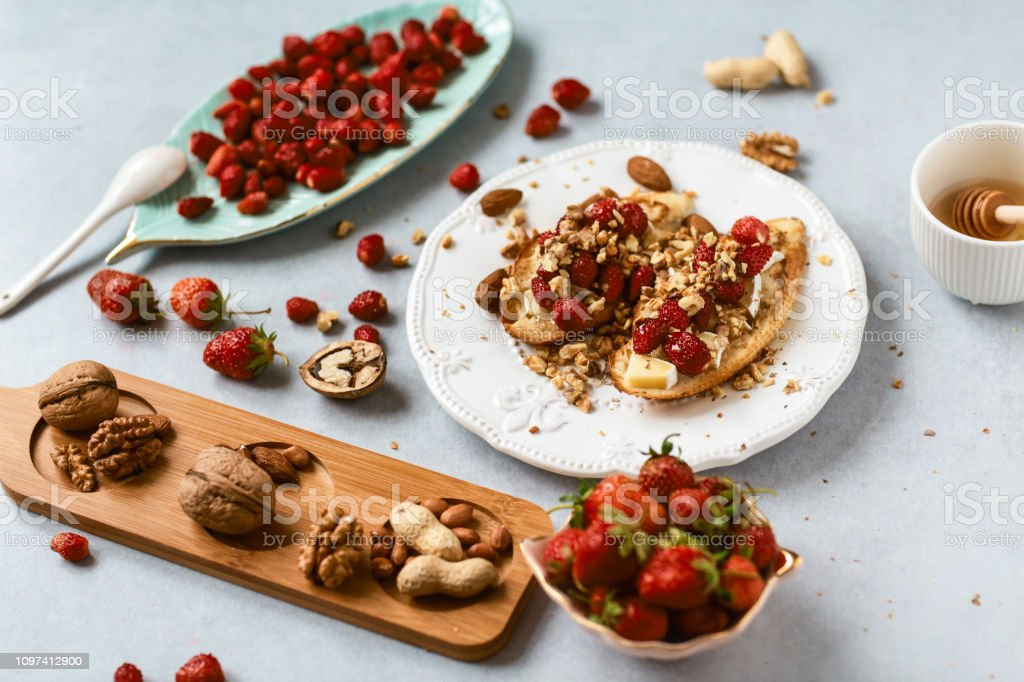 Bruschetta with strawberry, nuts and cheese camembert on wooden blue rustic background. Top side view, selective focus, Authentic lifestyle image stock photo