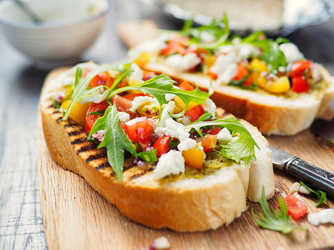 Home made freshness Bruschetta with fine chopped cherry tomatoes,rocket leaves and mozzarella cheese and green pesto.