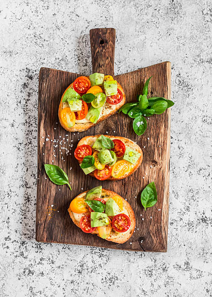 Bruschetta with tomatoes and avocado on rustic wooden cutting board - foto stock