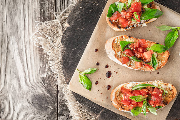 Bruschetta con pomodoro e basilico su tavola in legno vista dall'alto - foto stock