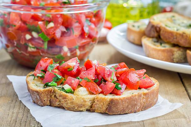 Bruschetta con pomodoro, erbe aromatiche e olio aglio formaggio sul pane - foto stock