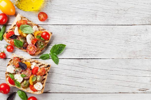 bruschetta mit tomaten, mozzarella und basilikum - brotschneidebrett stock-fotos und bilder