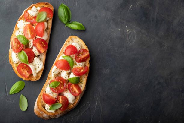 토마토, 모 짜 렐 라 치즈와 바 질에와 브루 쉐 타. 전통적인 이탈리아 전채 또는 스낵, 전채. 복사 공간 최고 볼 수 있습니다. 평면 배치 - 브루스케타 뉴스 사진 이미지