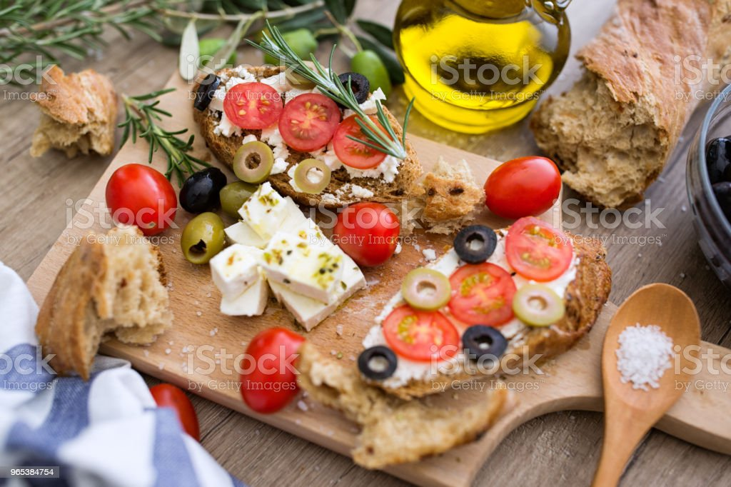 bruschetta with tomatoes, mozzarella cheese, olives and fresh vegetables royalty-free stock photo