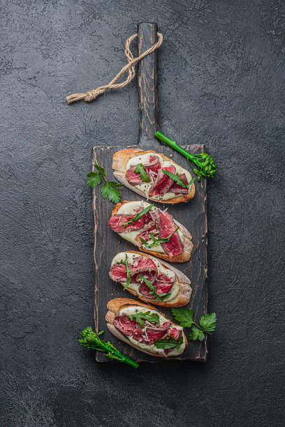 Bruschettas with beef on wooden board, flat lay stock photo