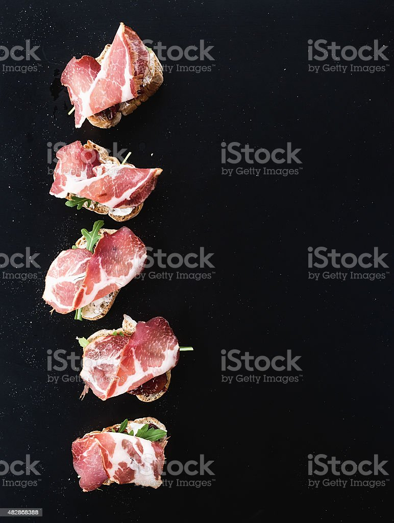 Bruschettas with prosciutto smoked meat, dried tomatoes and arugula over stock photo