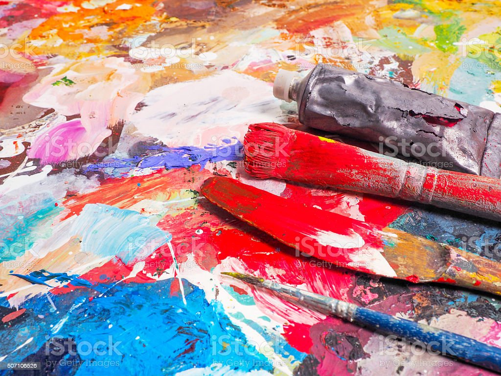 Brush and bright oil-paint palette for background stock photo