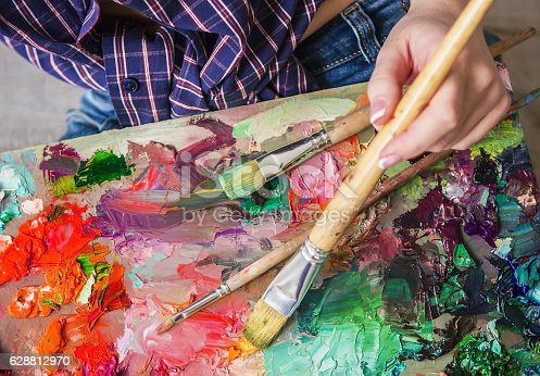 istock Brush and oil paints on a palette, paint a picture 628812970