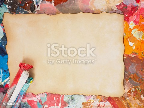 istock Brush and paper on oil-paint palette for background 507083530