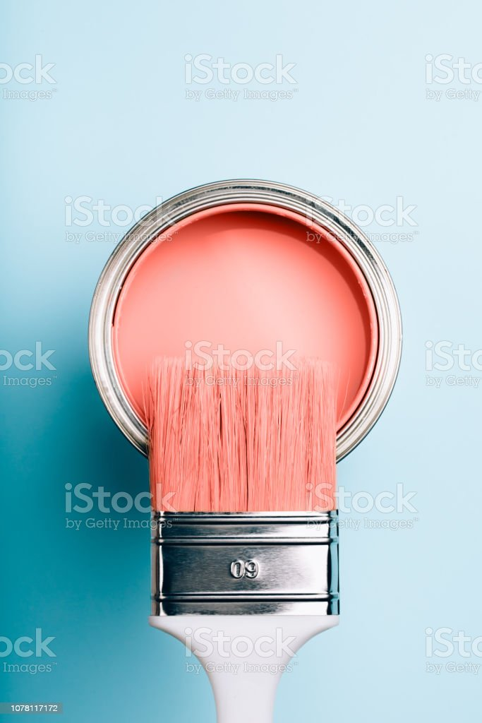 Brush on open can of Living Coral paint on blue pastel background Brush with white handle on open can of Living Coral paint on blue pastel background. Color of the year 2019. Main trend concept. 2019 Stock Photo