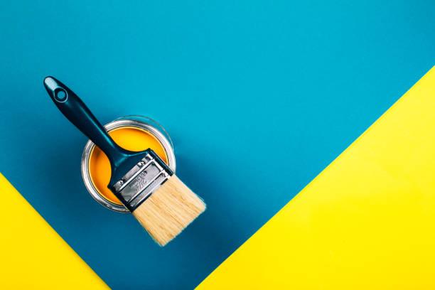 borstel op open kan gele kleur verf op gele en blauwe achtergrond. - verf stockfoto's en -beelden