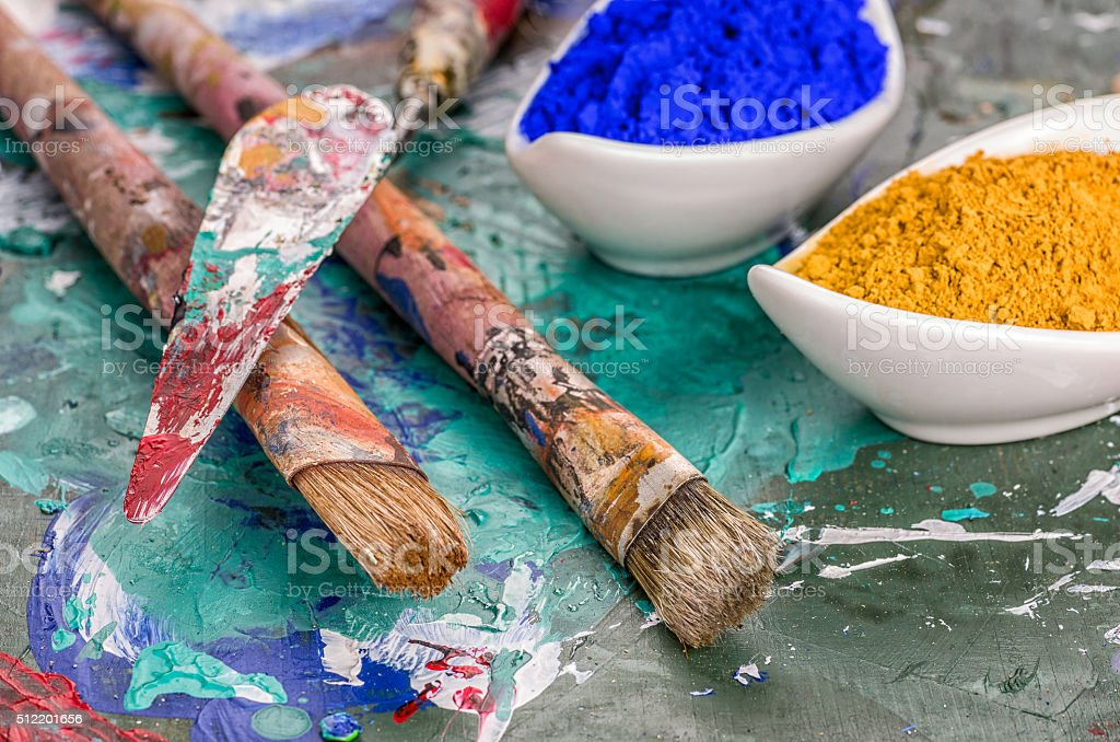 Brush, spatula and color pigments on a wooden palette stock photo
