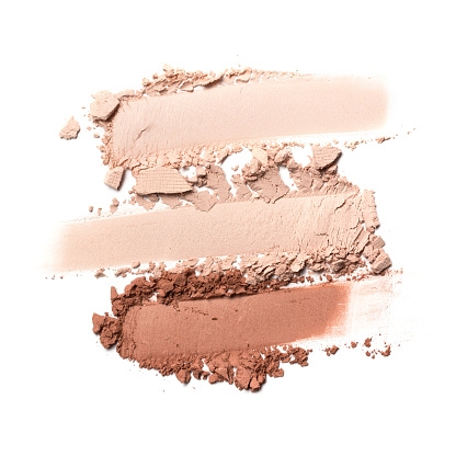 Brush strokes of crushed light beige and brown eye shadow as sample of cosmetic product isolated on white background