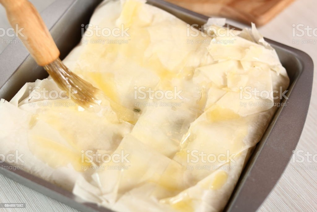 Brush top of pastry of with melted butter. Making Potato and Leek Filo Pie. Series. stock photo