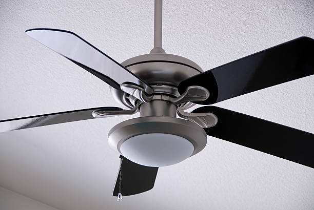 Brushed Metal Ceiling Fan A brushed metal ceiling fan with black fins. ceiling fan stock pictures, royalty-free photos & images