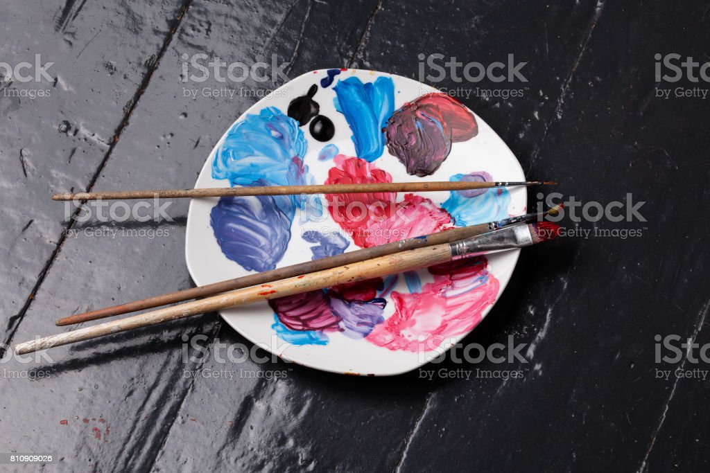 Brushes and palette on the floor stock photo