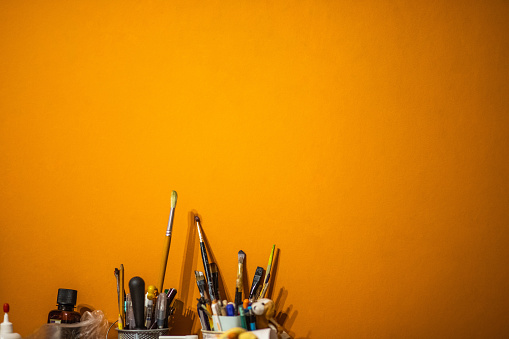 1084390994 istock photo brushes and pencils, stationery on the table against the background of the orange wall 1086093460