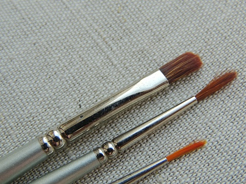 Brushes for painting on beige linen fabric background.