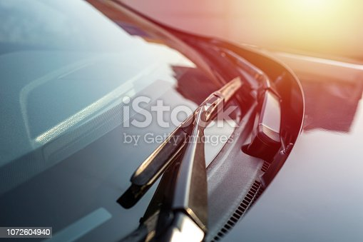 Brushes on the car glass with copy space. The work of windshield wipers - brushes and an evening sunbeam. toning