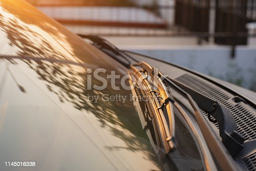 istock Brushes on the car glass with copy space. The work of windshield wipers - brushes and an evening sunbeam 1145016338