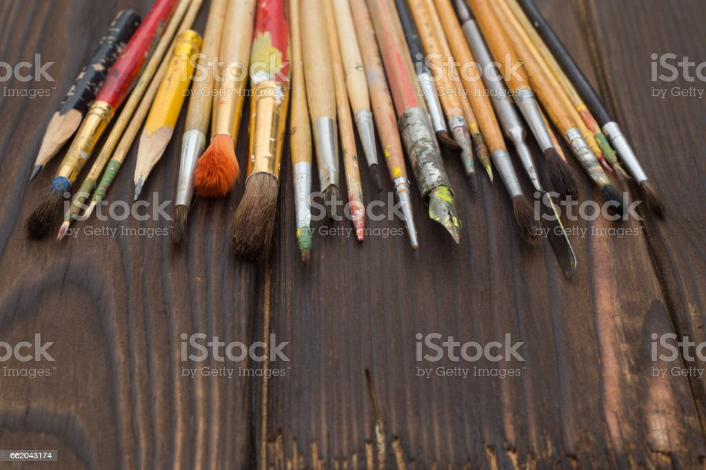 Brushes spread out on a dark wooden surface royalty-free stock photo