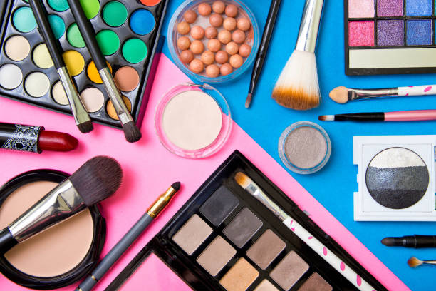 Brushes with an eyeshadow palette and lipstick in pink and blue geometric background Brushes with an eyeshadow palette and lipstick in pink and blue geometric background ceremonial make up stock pictures, royalty-free photos & images