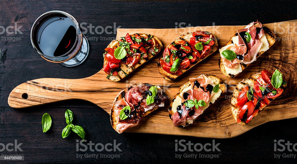 Brushetta set and glass of red wine. Small sandwiches with