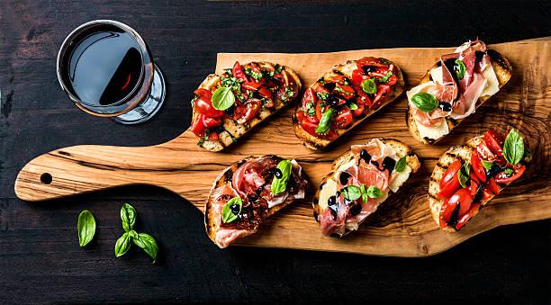 conjunto brushetta e taça de vinho tinto. sanduíches pequenos com - comida italiana - fotografias e filmes do acervo
