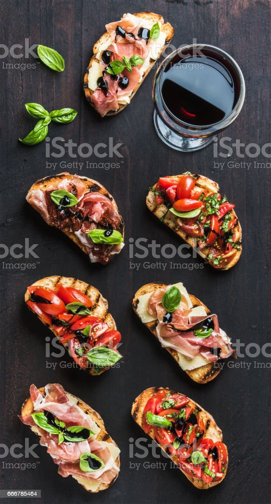 Brushetta set with glass of red wine. Small sandwiches on dark wooden background, top view - foto stock