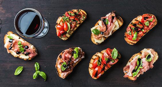 istock Brushetta snacks for wine. Variety of small sandwiches on dark 541602172
