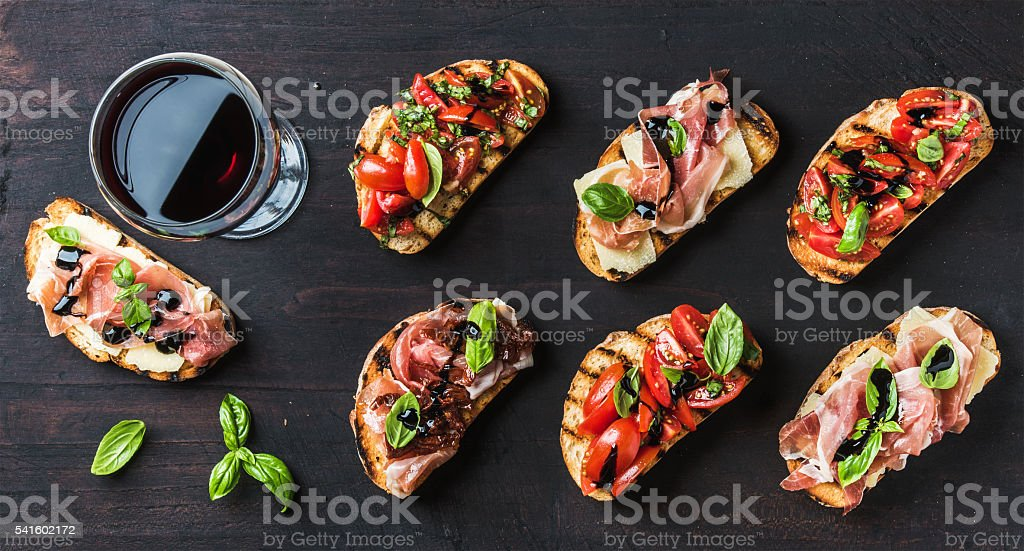 Brushetta snacks for wine. Variety of small sandwiches on dark stock photo