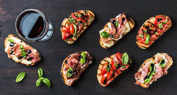 brushetta snacks for wine. variety of small sandwiches on dark - 브루스케타 뉴스 사진 이미지