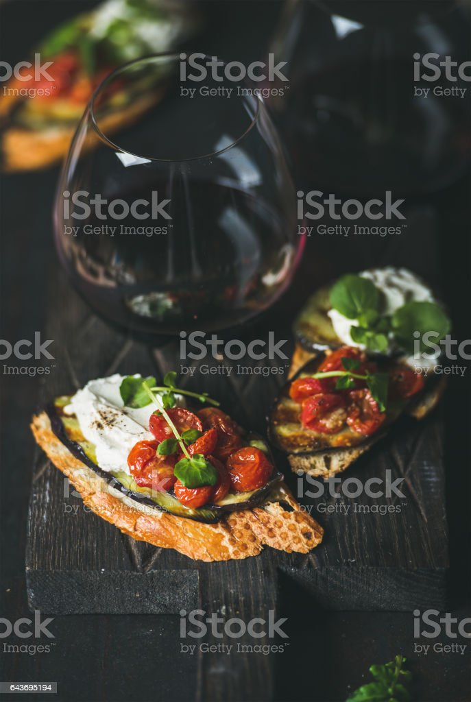Brushetta with eggplant, tomatoes, garlic, cream-cheese, arugula, glass of wine стоковое фото