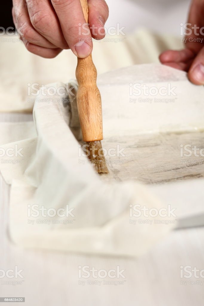 Brushing filo pastry sheet with butter. Making Potato and Leek Filo Pie. Series. stock photo