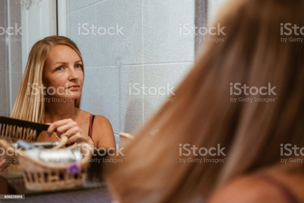 Brushing hair in bathroom stock photo