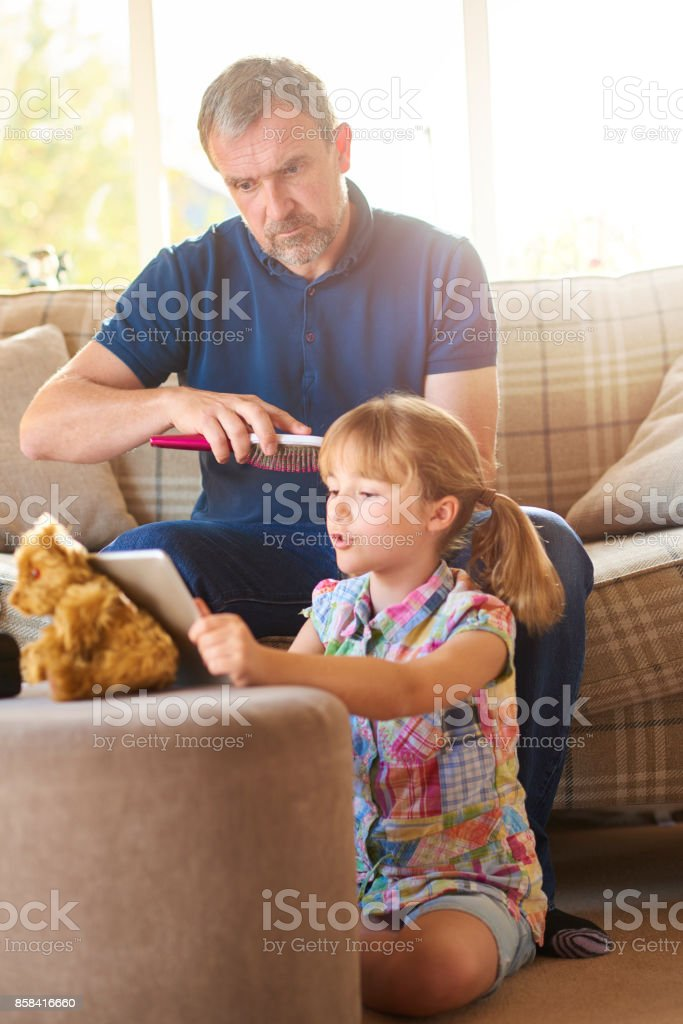 brushing his daughter's hair in the morning stock photo