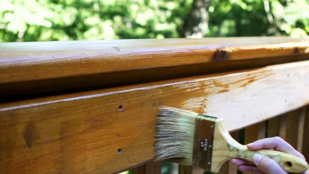 Brushing on stain on cedar deck. stock photo