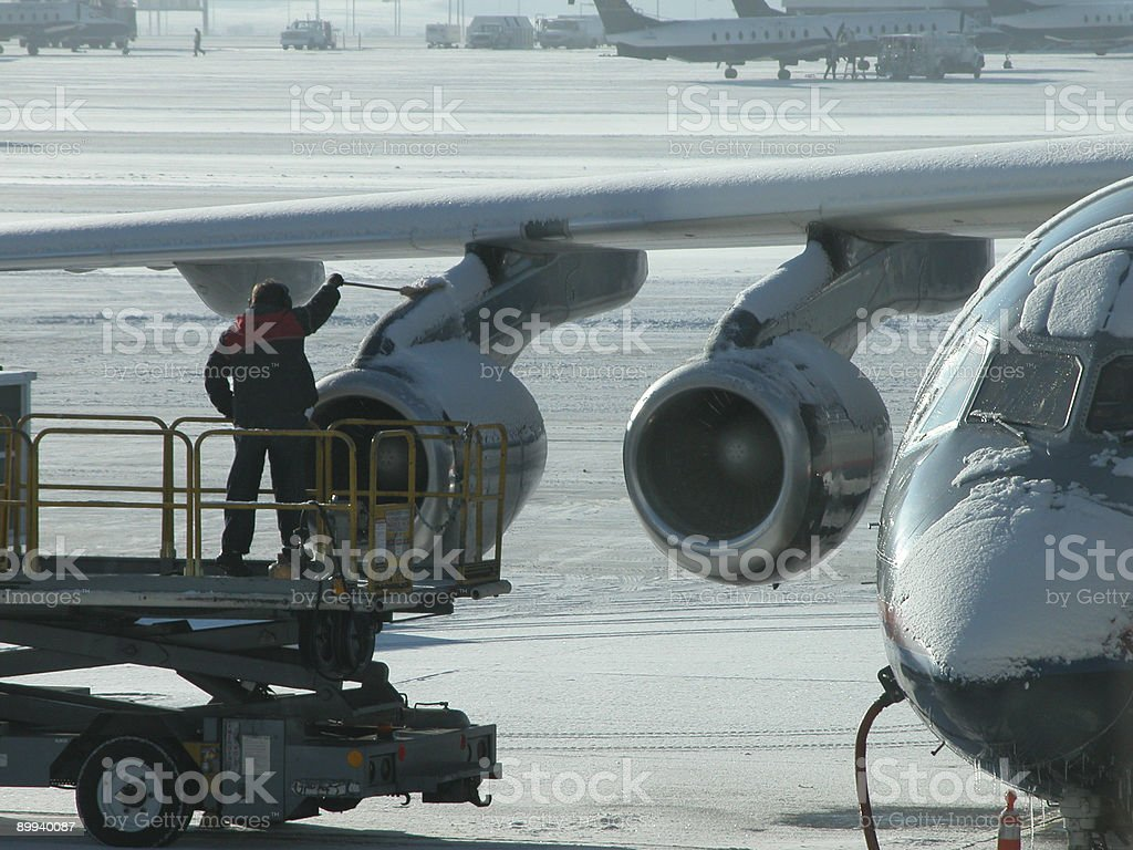 Brushing snow off airplane stock photo