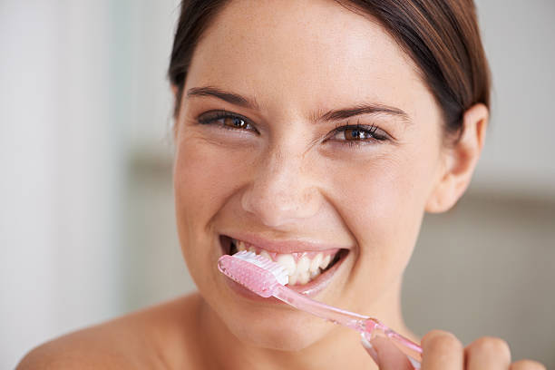 Brushing teeth can be exhilerating A gorgeous young brunette brushing her teeth in the morning toothbrush stock pictures, royalty-free photos & images