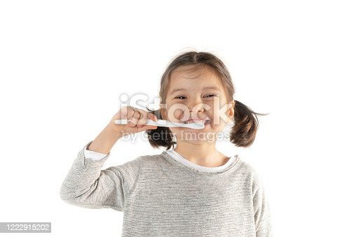 Caucasian toddler girl wearing a gray t-shirt is brushing her teeth in front of a blank gray wall and is looking at camera.