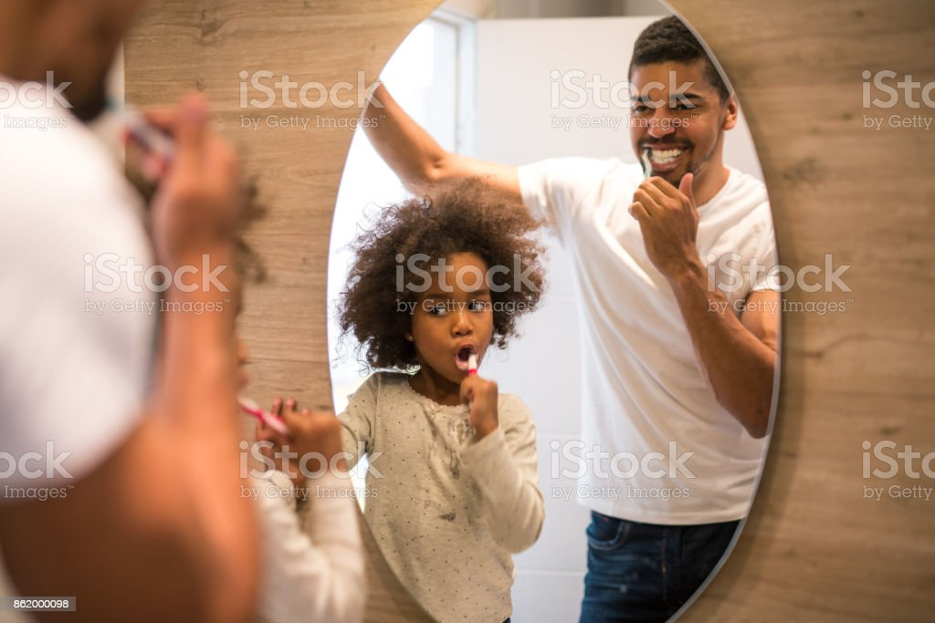 Brushing teeth with dad stock photo
