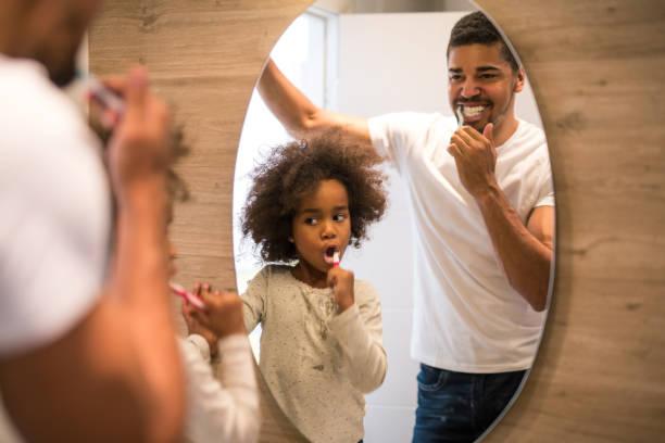 zähneputzen mit papa - zähne putzen stock-fotos und bilder
