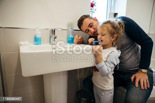 684029036 istock photo Brushing Teeth with Daddy 1193060457