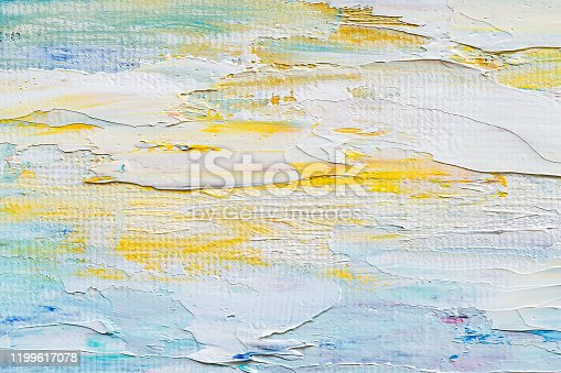 Brushstrokes of artistic oil paint on the canvas. Hand drawn painting. White, blue, yellow colored fragment of a modern artwork. Strokes of paint. Background and texture.
