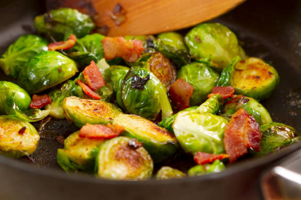 brussels sprouts cooking in a skillet - 小椰菜 個照片及圖片檔