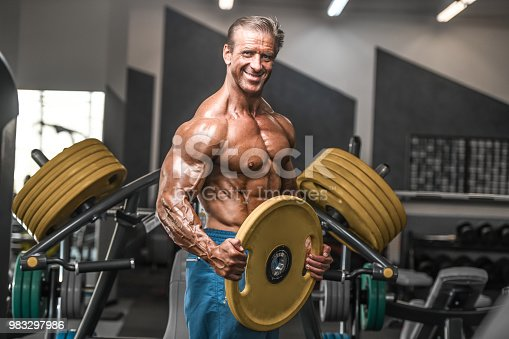 istock Brutal aged strong bodybuilder athletic men pumping up muscles with dumbbells 983297986
