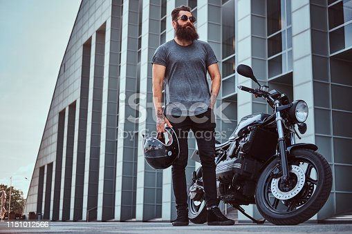 istock Brutal bearded male in sunglasses dressed in a gray t-shirt and black pants standing near his custom-made retro motorcycle against skyscraper. 1151012566