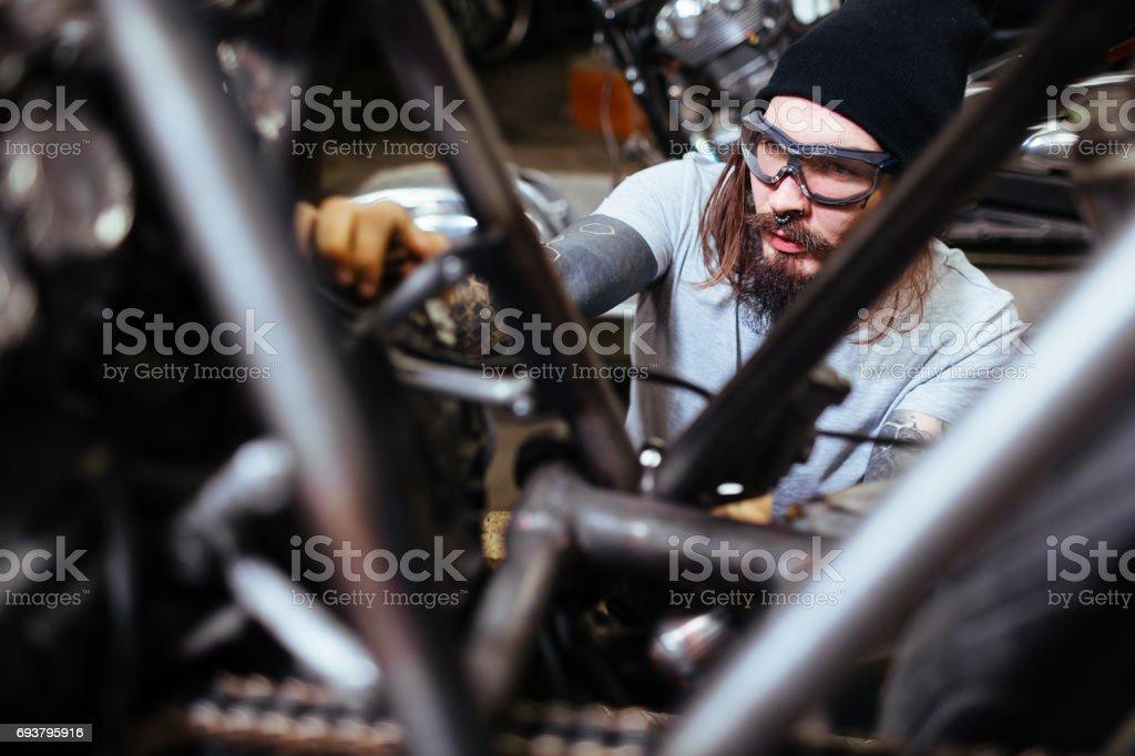 Brutal Biker Assembling Motorcycle in Garage - Royalty-free Adult Stock Photo