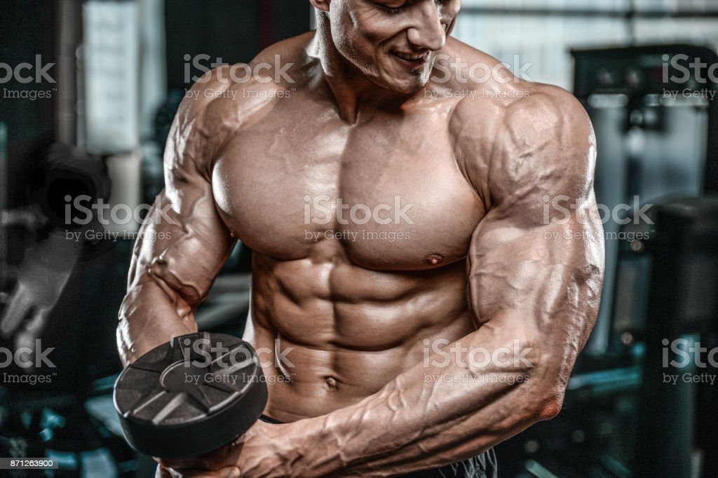 Brutal Caucasian bodybuilder working out in gym stock photo