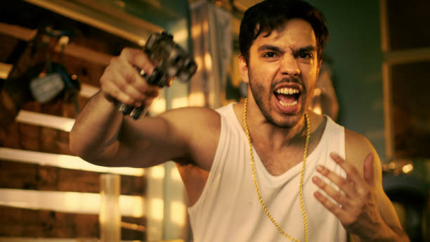Brutal Gang Member Gone Crazy Makes Threatening Gestures with a Gun. He Wears Gold Chain and Sleeveless Shirt. In the Background Abandoned Building with Boarded Up Windows. Brutal Gang Member Gone Crazy Makes Threatening Gestures with a Gun. He Wears Gold Chain and Sleeveless Shirt. In the Background Abandoned Building with Boarded Up Windows. drug cartel stock pictures, royalty-free photos & images